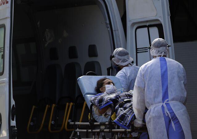 Agentes de saúde transportam paciente infectada pelo novo coronavírus ao hospital HRAN de Brasília, 3 de agosto de 2020