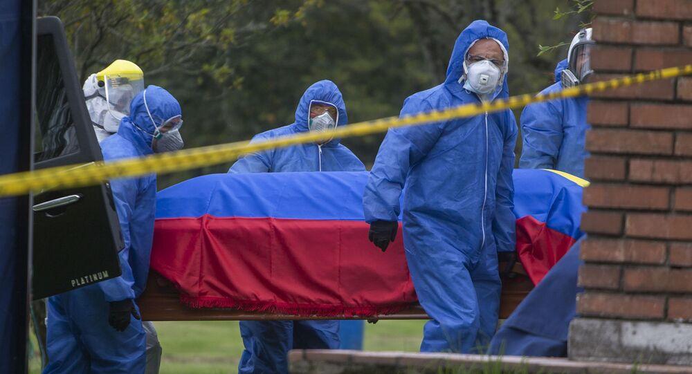 Agentes funerários carregam caixão de vítima da COVID-19 em Bogotá, na Colômbia.