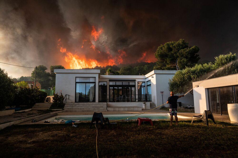 Homem usa mangueira de jardinagem para ensopar sua casa antes de evacuá-la, enquanto incêndio florestal arde por trás de sua residência em La Couronne, França