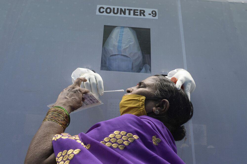 Mulher faz teste da COVID-19 em ponto de atendimento em Hyderabad, Índia