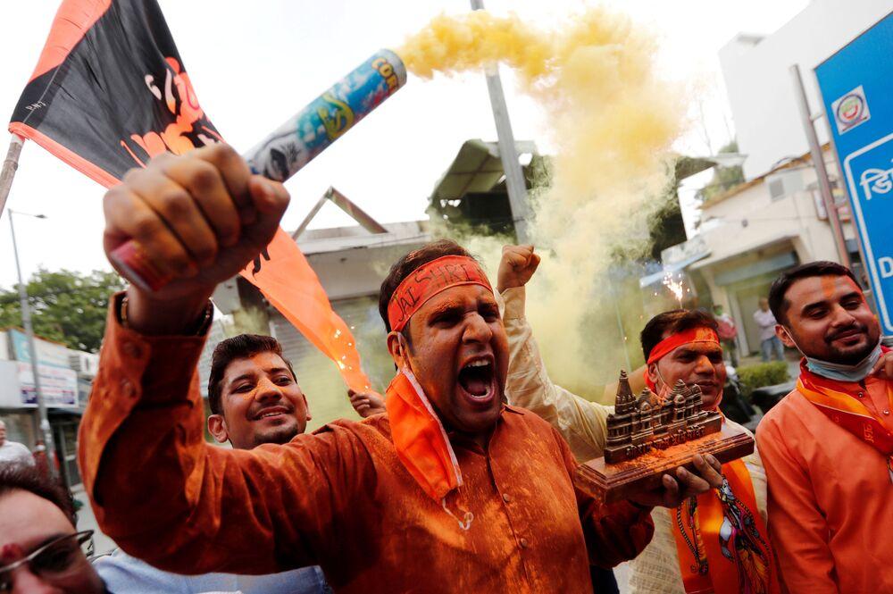Apoiador do partido indiano no poder Bharatiya Janata Party carrega em sua mão maquete do templo Ram, em Ayodhya, Índia