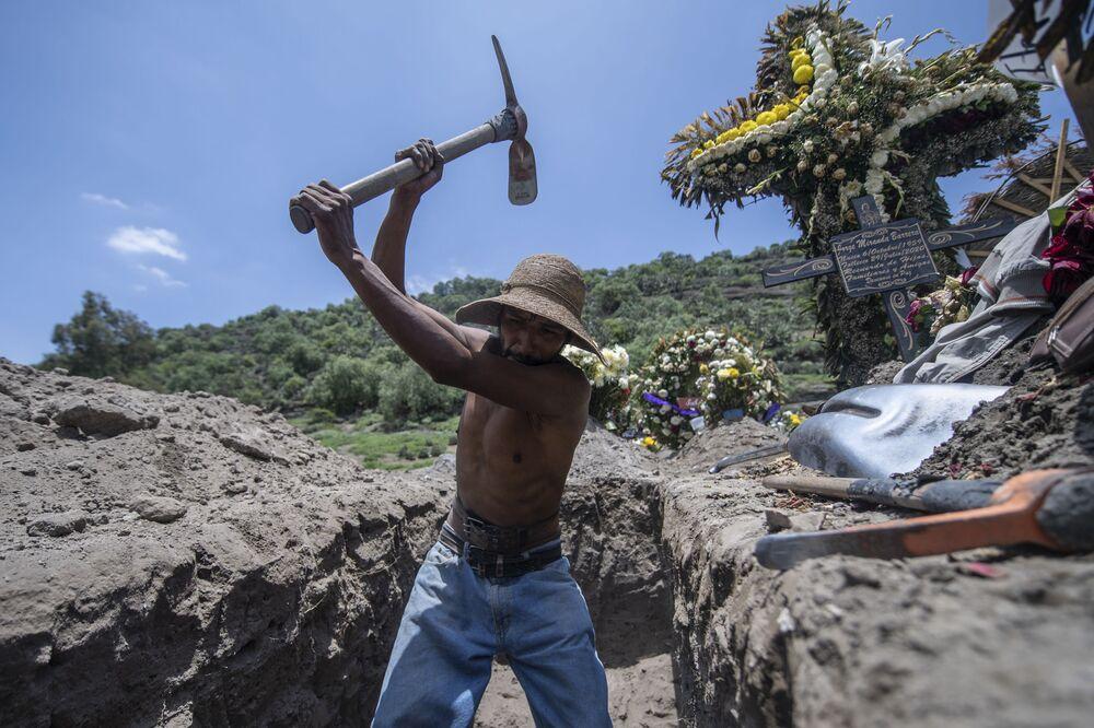 Coveiro abrindo nova cova durante funeral no cemitério San Miguel Xico, no México, durante a pandemia da COVID-19