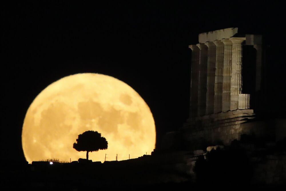 Lua surge no horizonte atrás das colunas do antigo Templo de Poseidon em cabo Sounion, cerca de 70 km de Atenas