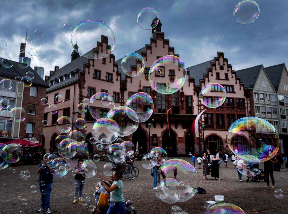 Artista de rua faz bolhas de sabão em frente à prefeitura de Frankfurt, Alemanha