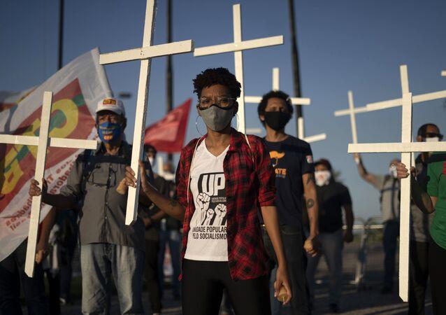 Manifestantes levam cruzes em homenagem às vítimas da COVID-19 e protesto contra a administração do presidente Jair Bolsonaro