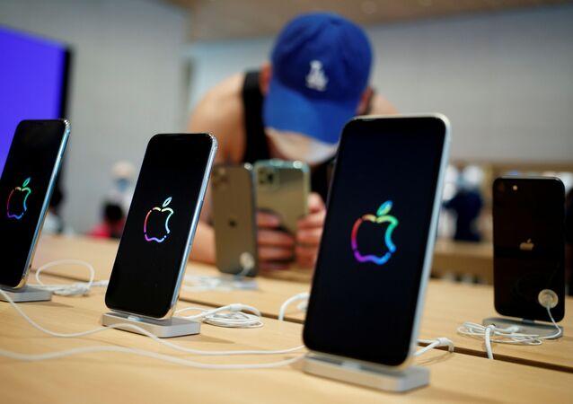 Em Pequim, na China, um homem tira fotos e Iphones dentro de uma loja da Apple após a reabertura do comércio em meio à pandemia da COVID-19, em 17 de julho de 2020.