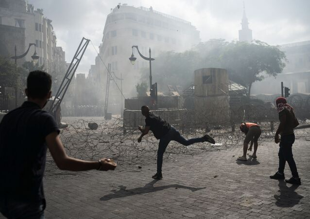 Manifestantes arremessam pedras contra a polícia no centro de Beirute em protesto contra o governo libanês