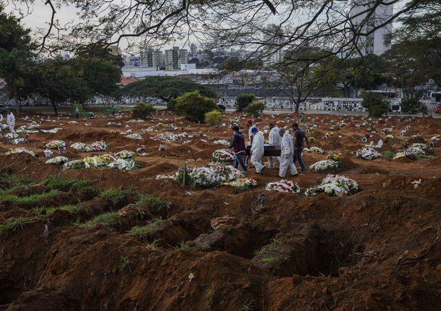 Sepultadores e parentes carregam caixão com vitima da COVID-19 no cemitério da Vila Formosa, na zona leste de Sao Paulo