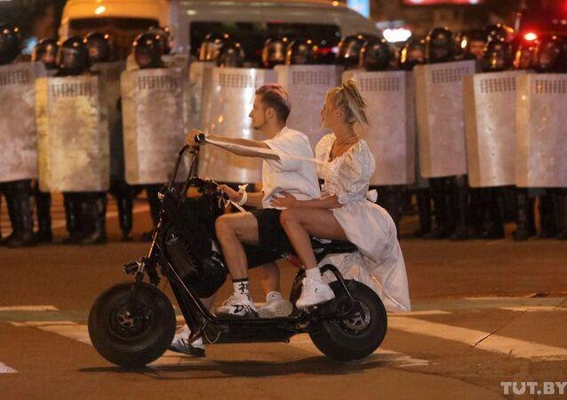 Casal passa de moto por tropa de choque bielorrussa, em meio a protestos na capital Minsk, 9 de agosto de 2020