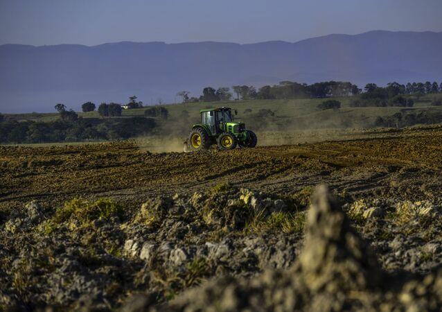 Trator prepara a terra para o plantio de soja na zona rural da cidade de Pindamonhangaba, no interior de São Paulo