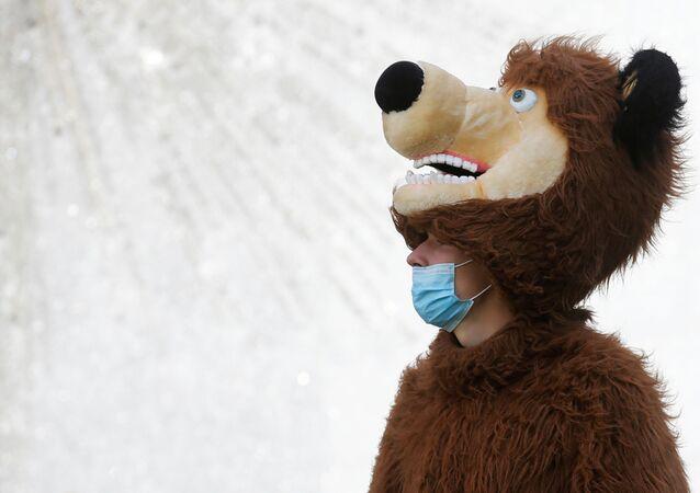 Homem com fantasia de urso usa máscara protetora no centro de Kiev, na Ucrânia, 11 de agosto de 2020