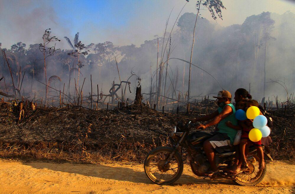 Família passa de moto ao lado de fumaça de incêndio na floresta amazônica próximo de Lábrea, no Amazonas
