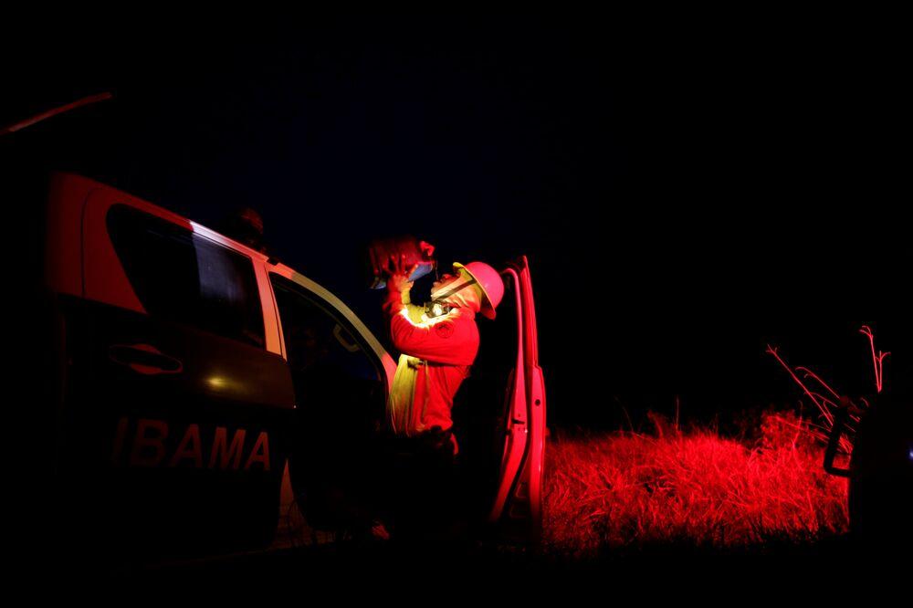 Membros do IBAMA tomam água enquanto combatem focos de incêndio em Apuí, no estado do Amazonas