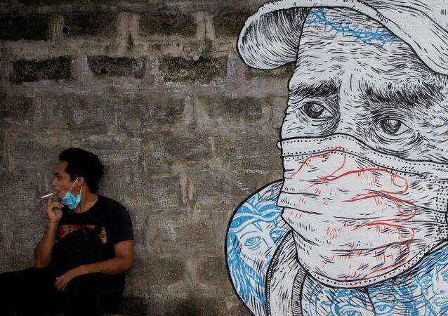 Homem fuma cigarro ao lado de pintura de homem usando máscara protetora em meio à disseminação da doença do coronavírus (COVID-19) na Cidade Quezon, Grande Manila, Filipinas, 30 de julho de 2020