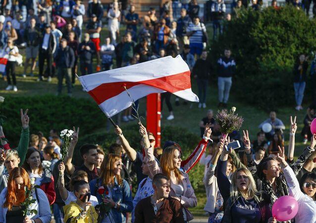 Multidão de jovens com bandeira branca e vermelha protesta em Minsk, capital da Bielorrússia