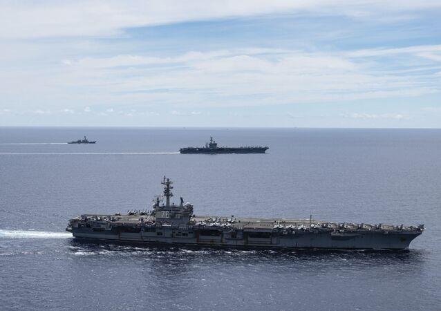 Porta-aviões USS Ronald Reagan (CVN 76, à frente) e o USS Nimitz (CVN 68, atrás) dos Grupos de Porta-Aviões navegam juntos em formação, no mar do Sul da China, 6 de julho de 2020