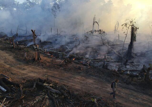 Homem anda em meio aos incêndios na floresta amazônica.