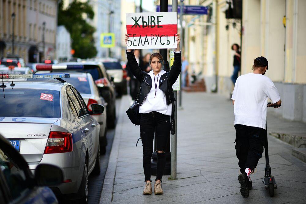Uma jovem com cartaz Viva a Bielorrússia! em frente à embaixada da Bielorrússia em Moscou em meio aos protestos após eleições presidenciais