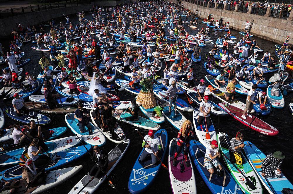 Participantes do festival internacional de surfe com remo Fontanka SUP no rio Moika em São Petersburgo, na Rússia