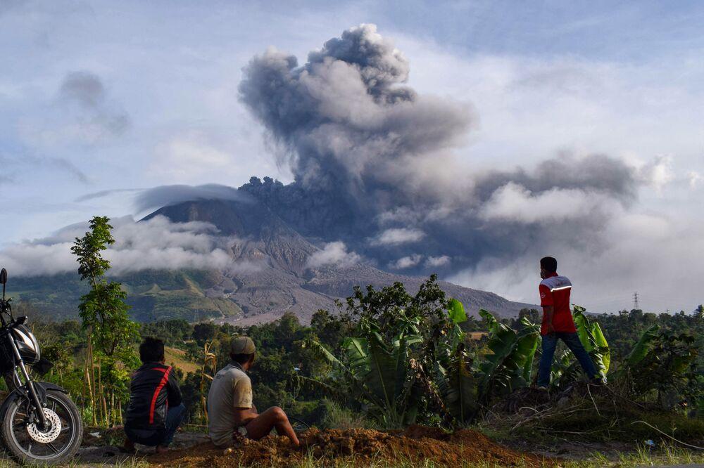 Residentes de um vilarejo na ilha de Sumatra olhando a erupção do vulcão Sinabung, que espalha um pilar de cinzas de dois quilómetros