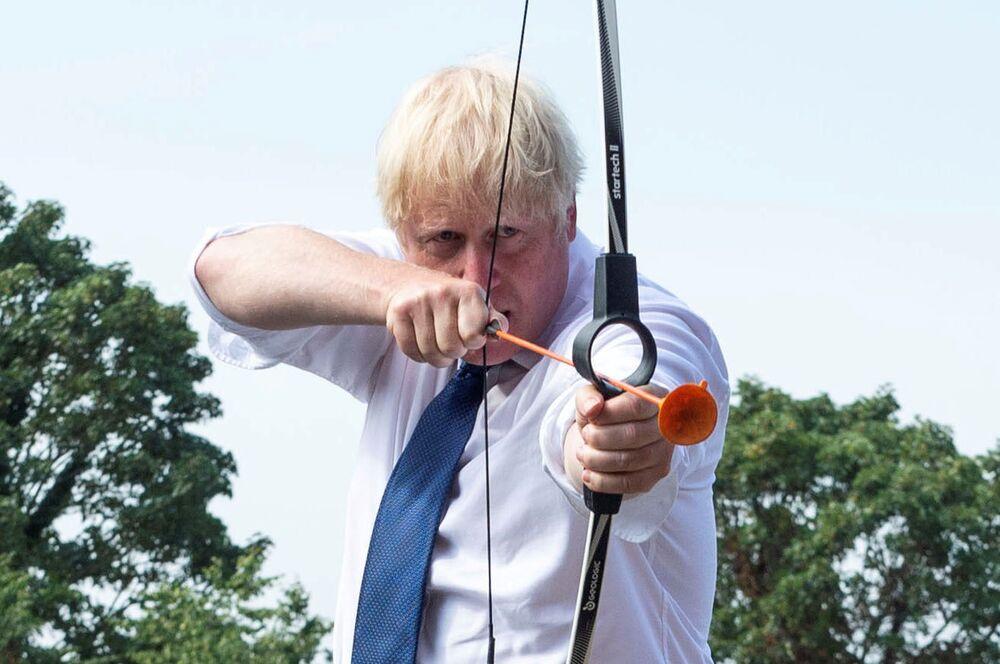 Premiê britânico Boris Johnson disparando arco em campo de educação em Londres