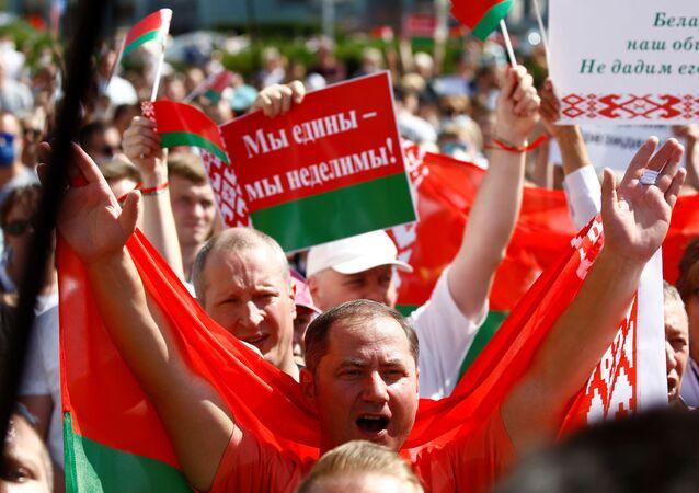 Participantes de manifestação pró-Lukashenko na praça da Independência em Minsk, Bielorrússia