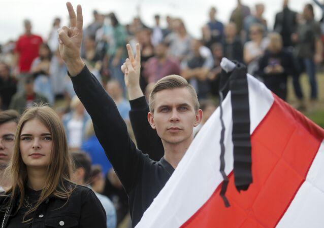 Pessoas seguram bandeira diante de multidão em protesto em Minsk, na Bielorrússia