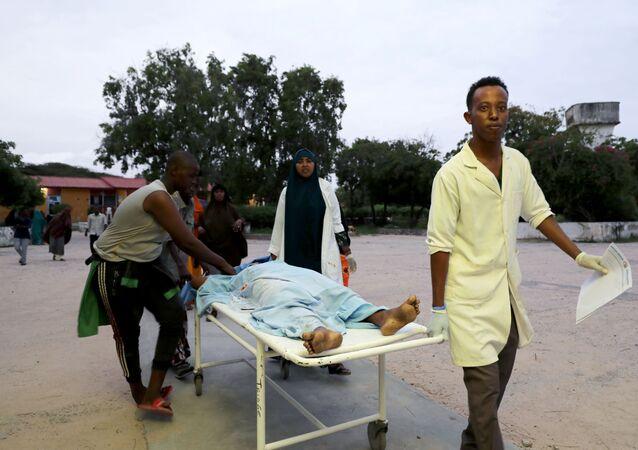 Em Mogadíscio, capital da Somália, equipe médica e civis carregam uma pessoa ferida após uma explosão de carro-bomba em hotel de luxo na praia de Lido, em 16 de agosto de 2020.