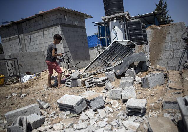 Garoto palestino observa danos causados em sua casa por ataques aéreos de Israel contra a Faixa de Gaza