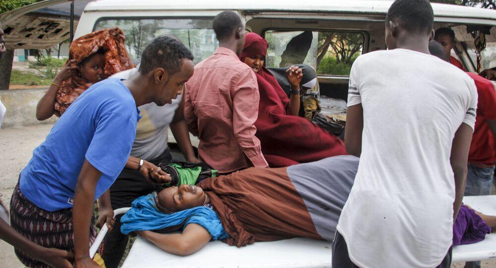 Médicos e civis ajudam a carregar mulher ferida em ataque com carro-bomba em hotel em Mogadíscio, na Somália