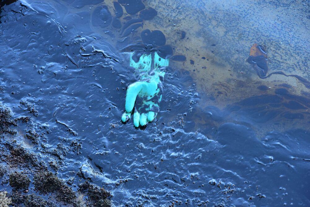 Luva de borracha flutua sobre o petróleo derramado enquanto voluntários participam de operação de limpeza nas Ilhas Maurício