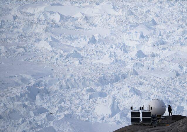 Mulher ao lado de uma antena em um acampamento da Universidade de Nova York (EUA) na geleira Helheim, Groenlândia, 27 de agosto de 2019