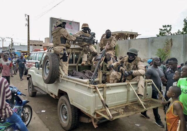 Em Bamaco, tropas do Mali e cidadãos malineses se juntam em frente à residência do presidente do país, Ibrahim Boubacar Keita, em meio a um motim militar em 18 de agosto de 2020.