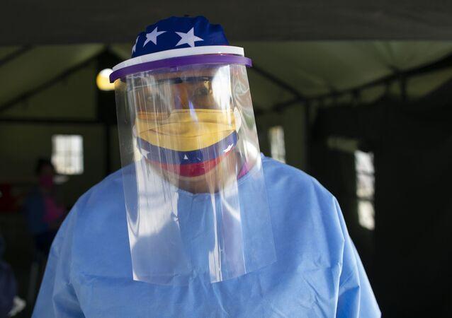 Mulher com roupa de proteção e máscara com bandeira da Venezuela administra testes para coronavírus em Caracas