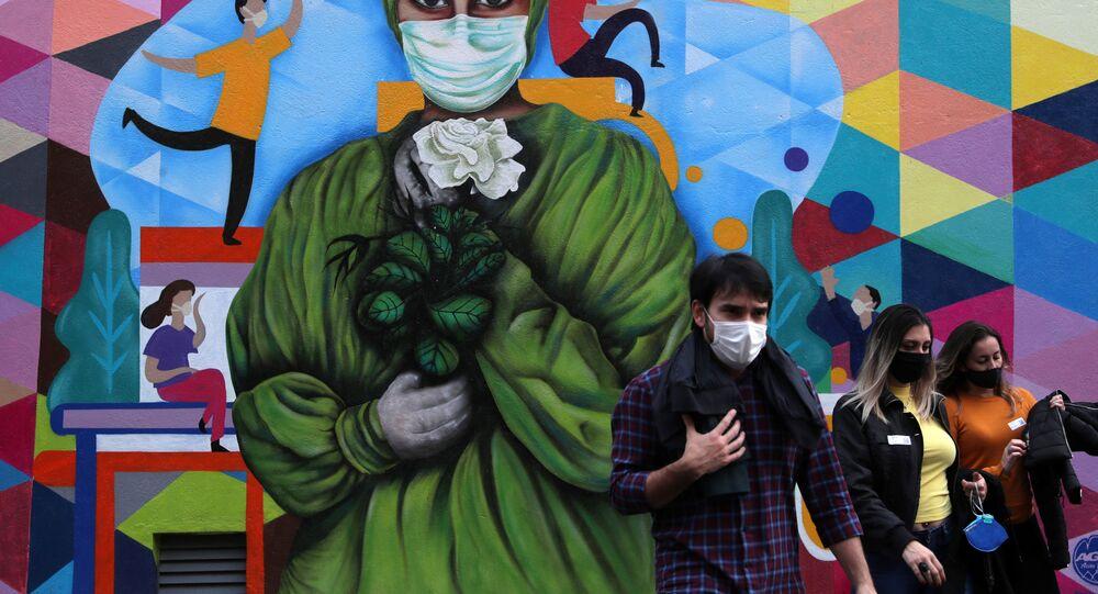 Pessoas caminham em frente a grafite em homenagem a trabalhadores de saúde durante pandemia do coronavírus no Hospital das Clínicas, em São Paulo