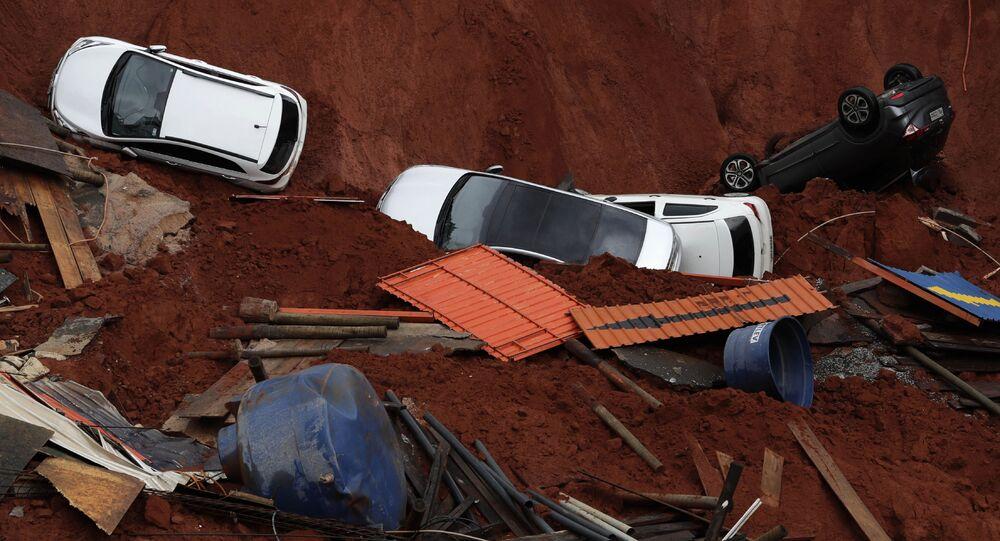 Veículos no fundo de um canteiro de obras devido ao colapso de uma estrada, causado por fortes chuvas no centro de Brasília, Brasil, 10 de dezembro de 2019
