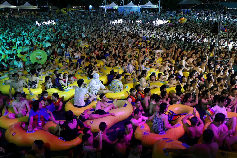 Pessoas desfrutam de uma festa de música dentro de uma piscina no Wuhan Maya Beach Park, em Wuhan, China