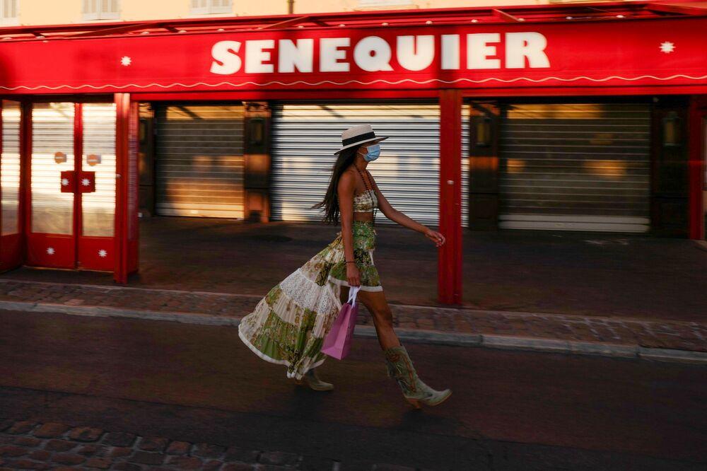 Mulher com máscara protetora caminha ao longo do Le Cafe Senequier, fechado, situado no porto de Saint-Tropez