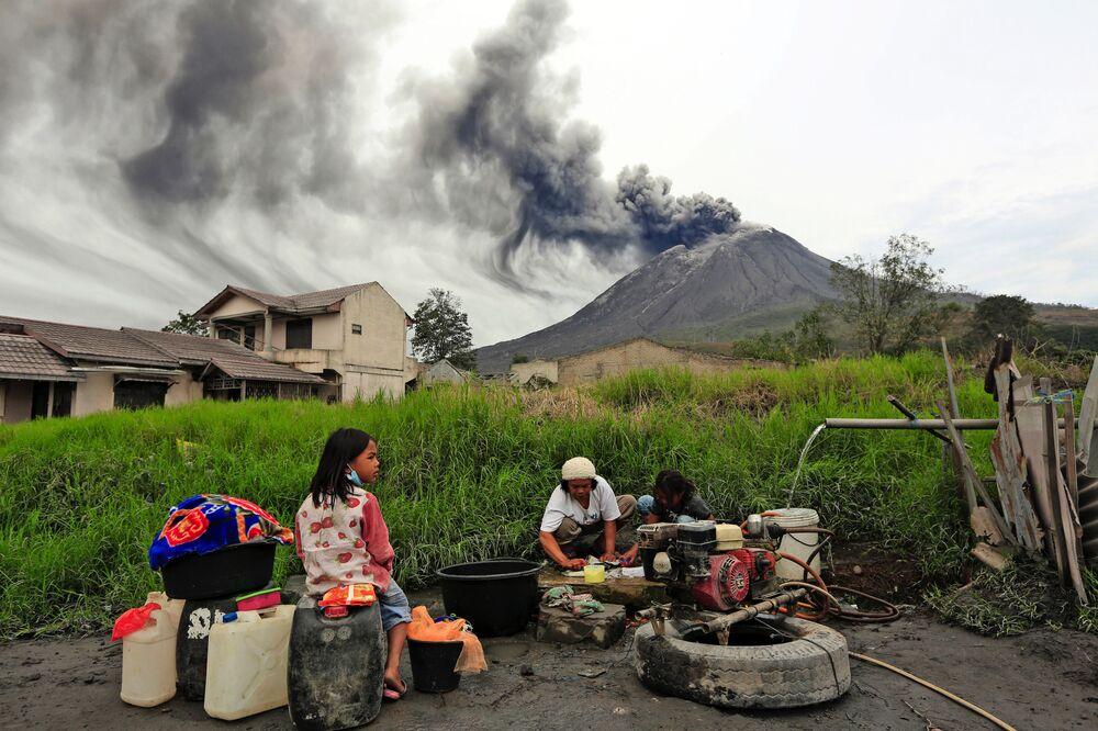 Pessoas lavam roupa perto do vulcão ativo Sinabung, Indonésia