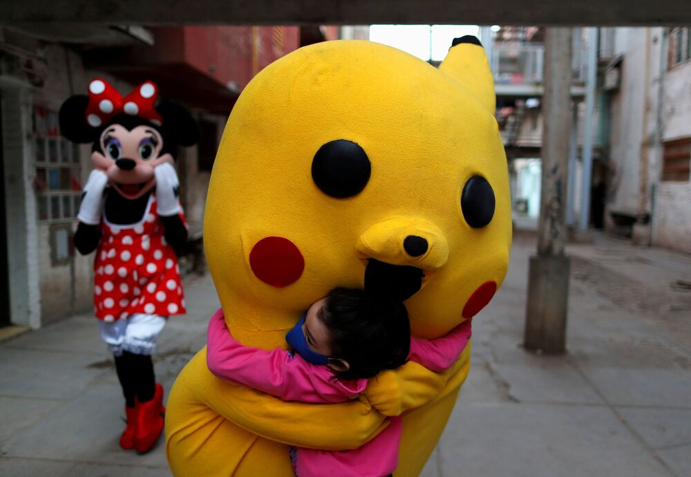 Um voluntário vestido com um traje do Pokémon Pikachu abraça uma criança durante o Dia da Criança em Buenos Aires