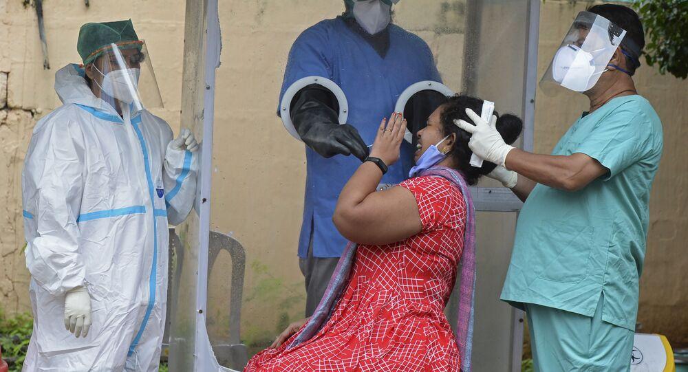 Coleta de amostra por esfregaço de uma mulher em um centro gratuito de testes do coronavírus em Hyderabad, Índia