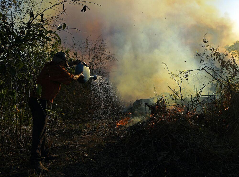 Agricultor tenta combater incêndio em uma reserva natural na floresta amazônica, Brasil