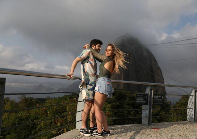 Casal abraçado com o monte Pão de Açúcar em fundo, Rio de Janeiro