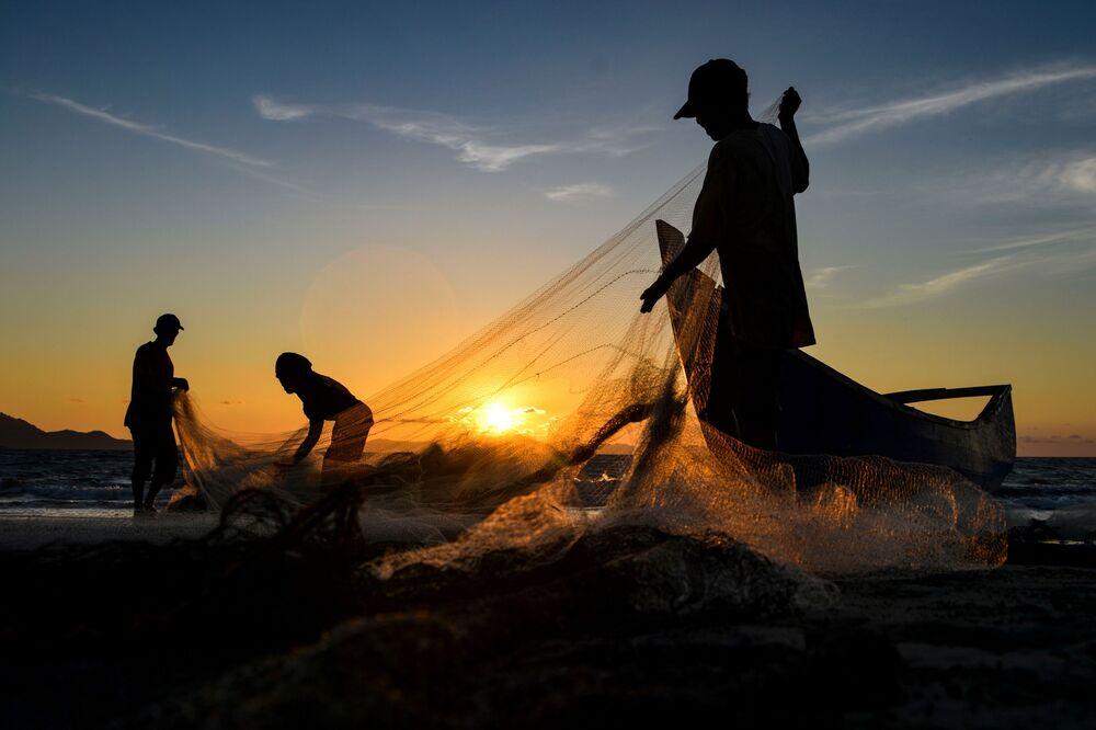 Pescadores limpam suas redes após a pesca ao pôr do sol em Banda Aceh, Indonésia