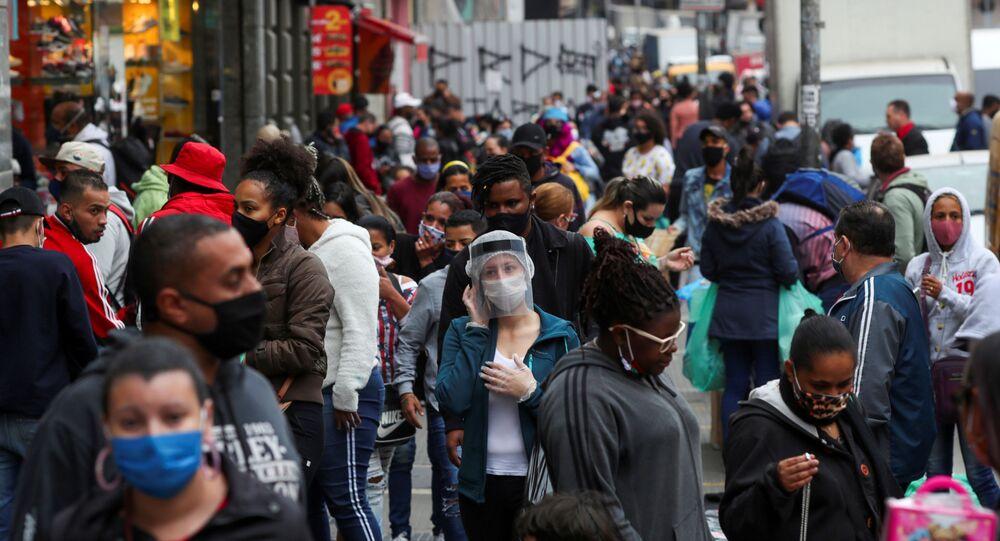 Em São Paulo, pessoas caminham nas ruas usando proteção facial e máscaras contra a COVID-19, em 15 de julho de 2020.