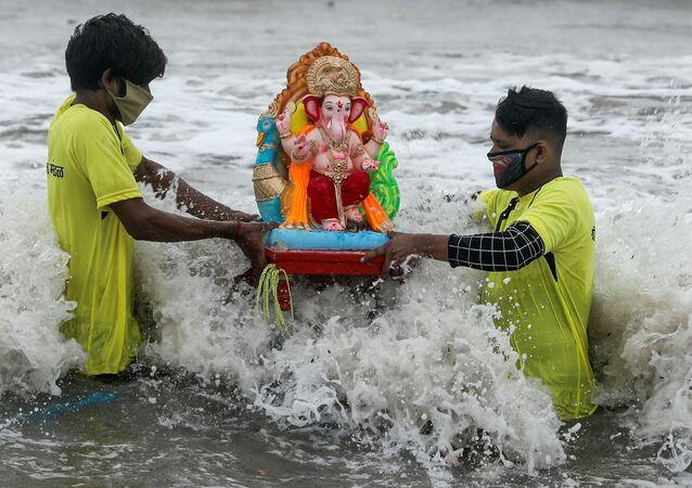 Jovens de máscaras para se proteger do coronavírus carregam estátua do deus Ganesh em Mumbai, na Índia