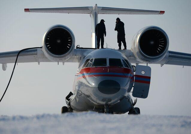 Dois técnicos abastecem o avião An-74 em uma ilha que é parte da Terra do Norte