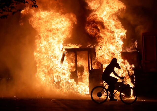 Homem de bicicleta passa em frente a caminhão em chamas na frente ao Tribunal do condado de Kenosha, no estado de Wisconsin, nos Estados Unidos, após protesto pelos tiros disparados pela polícia contra o homem negro Jacob Blake.