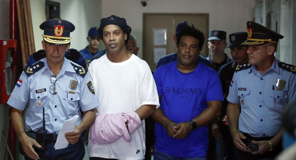Em Assunção, no Paraguai, o ex-jogador de futebol, Ronaldinho Gaúcho (a segundo a partir da esquerda), caminha ao lado irmão, Roberto de Assis (o primeiro à direita de Ronaldinho), sendo escoltado pela polícia paraguaia, em 7 de março de 2020.