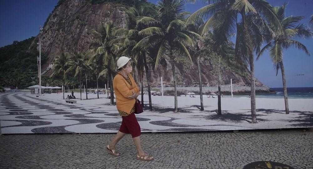 Mulher caminha em frente ao Hotel Hilton, no Rio de Janeiro, fechado por conta da pandemia da COVID-19.